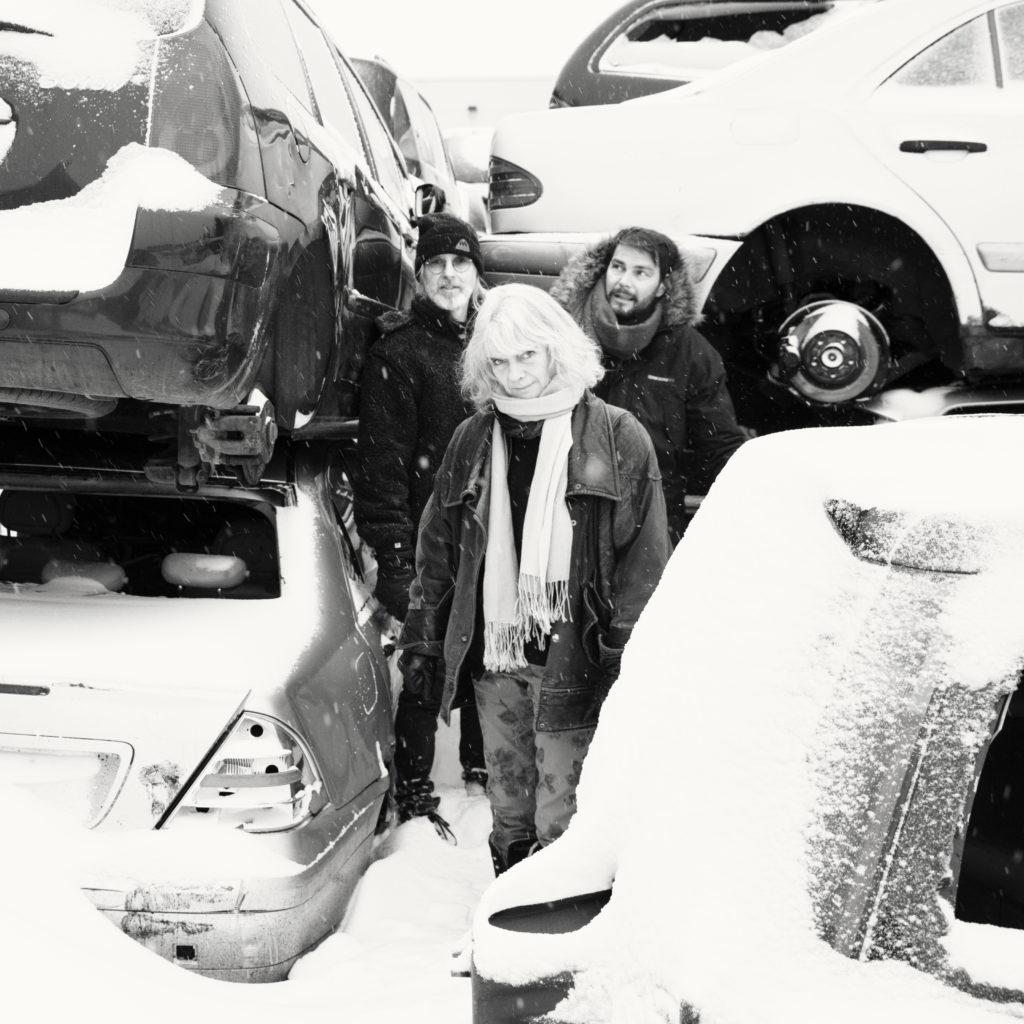 Anne-Marie Giørtz, Eivind Aarseth (briller) og Peter Baden, på Stokstad bilopphuggeri, for fotografering til albumet