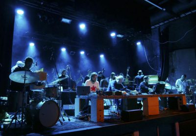 Tjue musikere med papirposer på huet